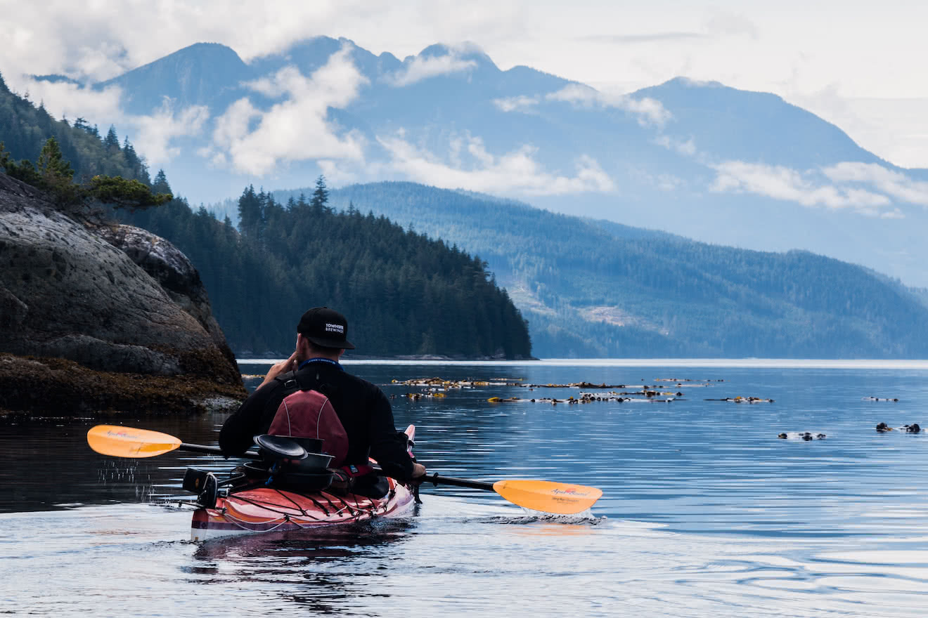 A kayaker looks about in wonder at the beautiful British Columbia coast