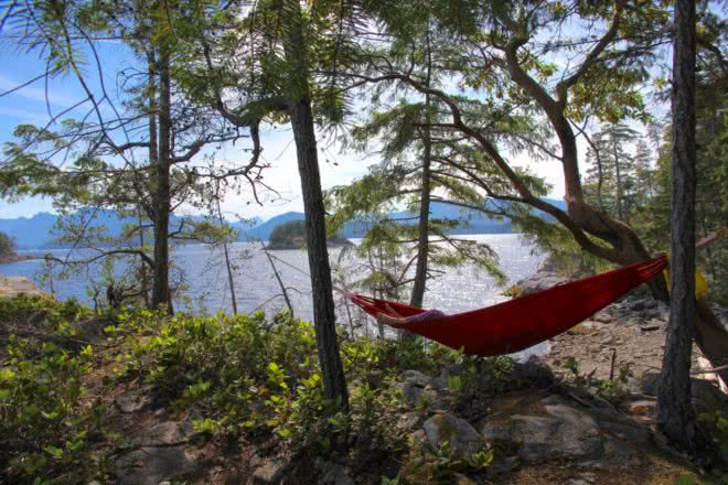 A guest lazing in a hammock overlooking Desolation Sound on one of our Chill & Immerse resort packages