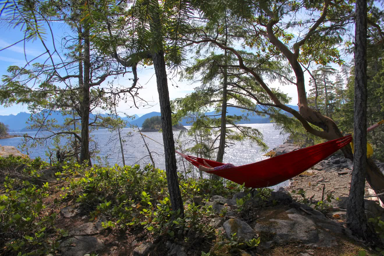 A guest lazing in a hammock overlooking Desolation Sound on one of our Chill & Immerse glamping resort packages