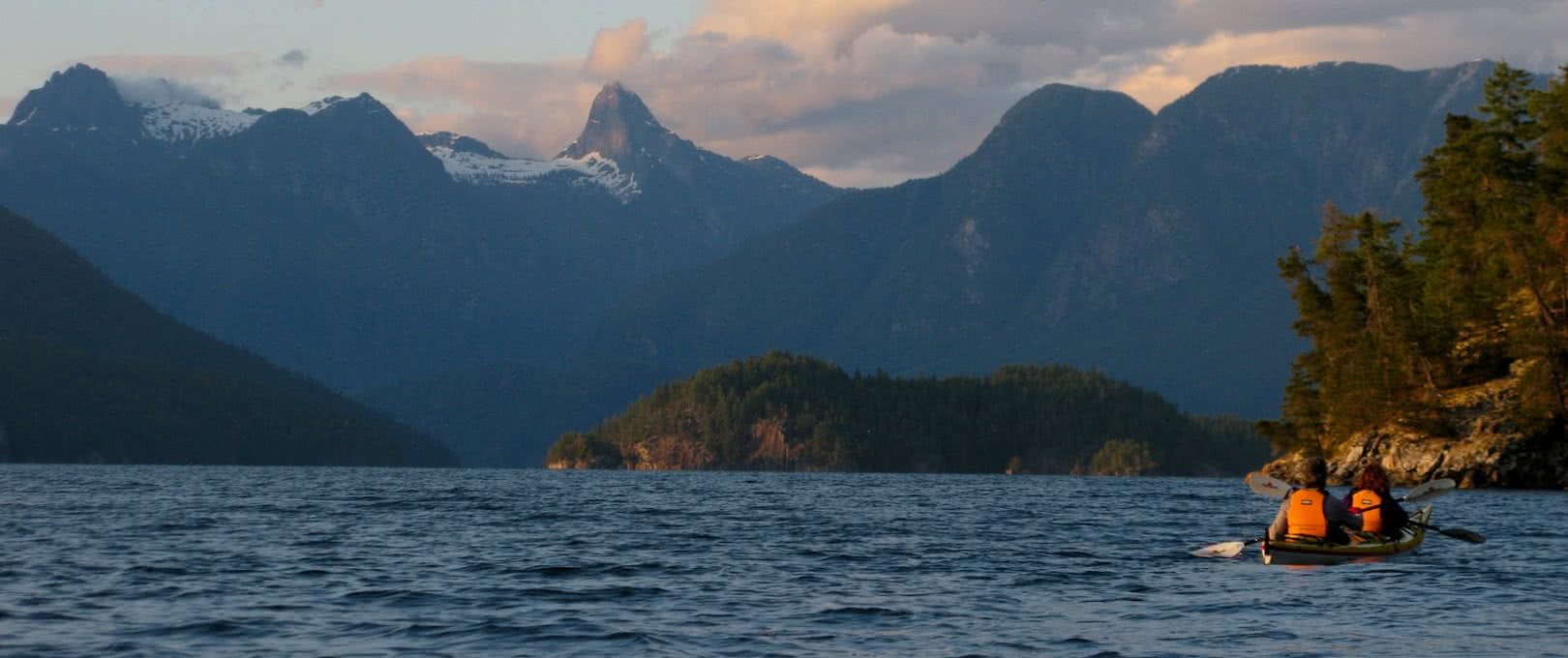 Two kayakers paddling towards Mount Denman and British Columbia's Coast Mountain range