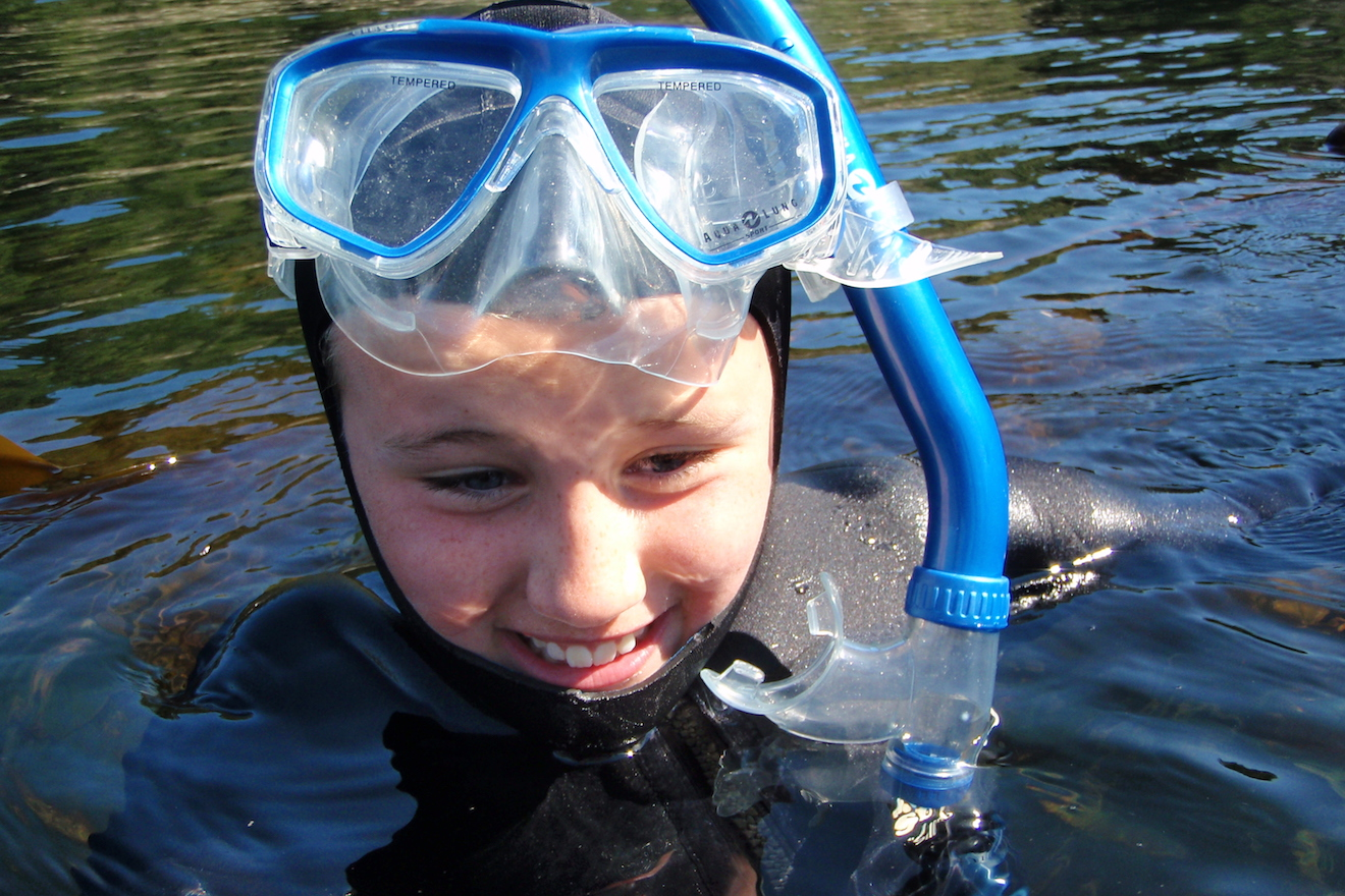 A happy young snorkeler comes up for air in Desolation Sound
