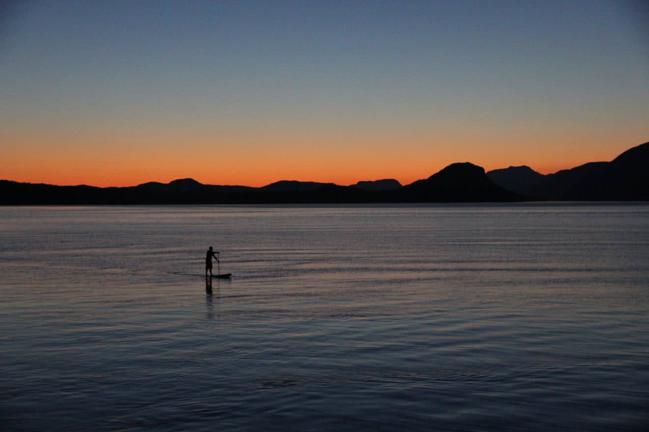 A guest paddle boarding as the sun sets on coastal British Columbia
