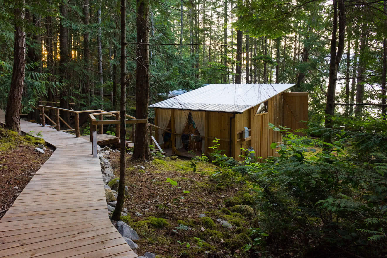 A cedar boardwalk connects handcrafted cabanas at this west coast eco resort
