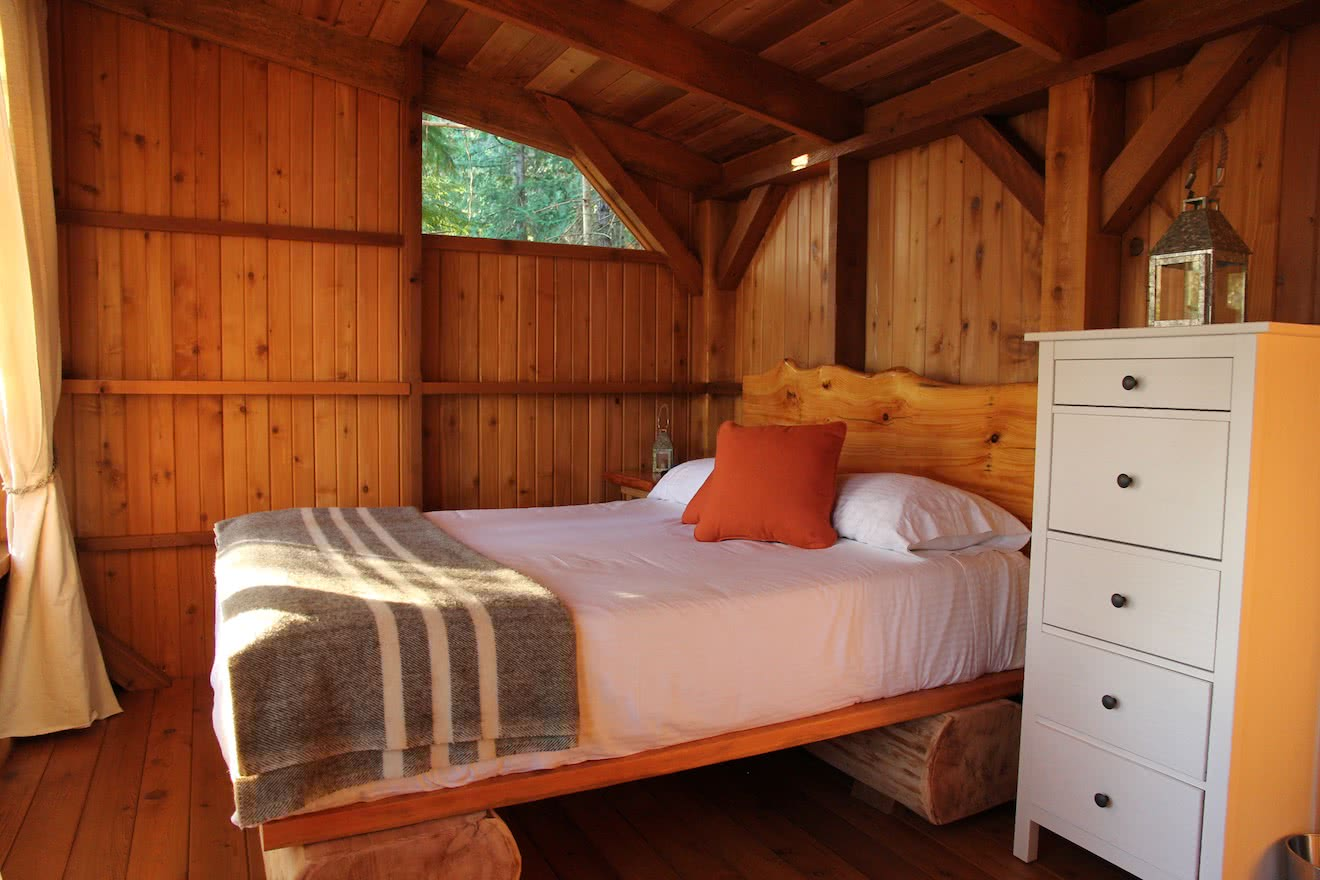 Interior shot of an eco resort cabana accommodation with log bed in Desolation Sound