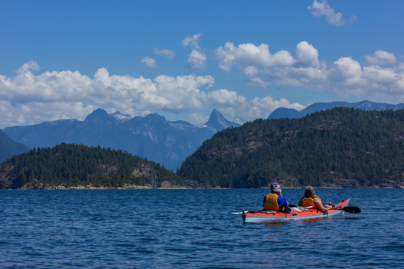 Two guests exploring Desolation SOund and the Coast Mountains on a double kayak