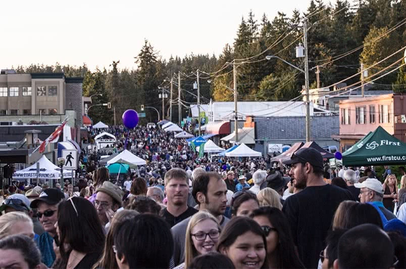 A crowd of people walking down the street during the Blackberry Street Festival in Powell River