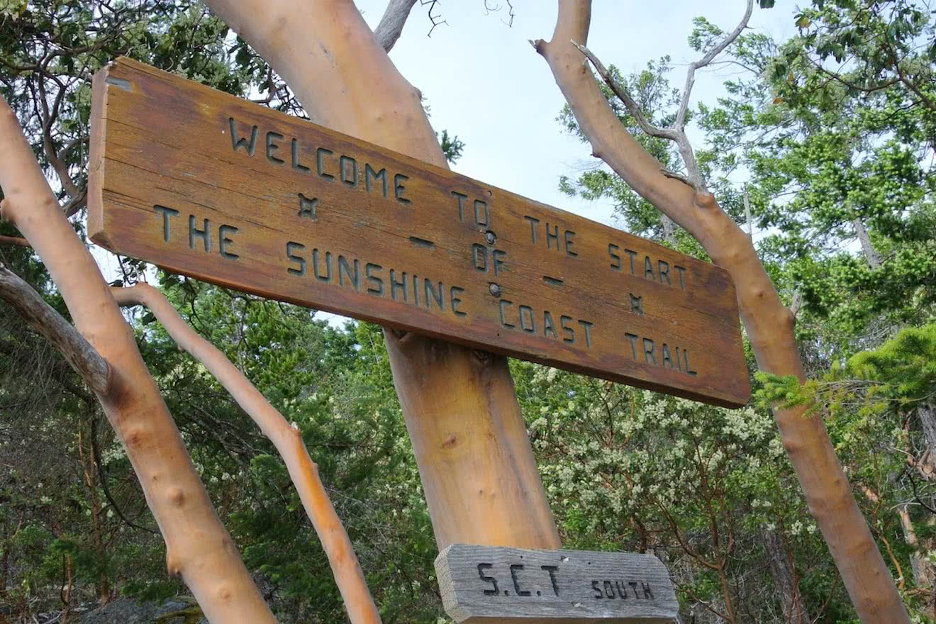 "A sign at the start of a hiking trail in Desolation Sound: ""Welcome to the start of the Sunshine Coast Trail"""