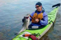 A kayaker comes to shore after catching a huge salmon while fishing in Desolation Sound
