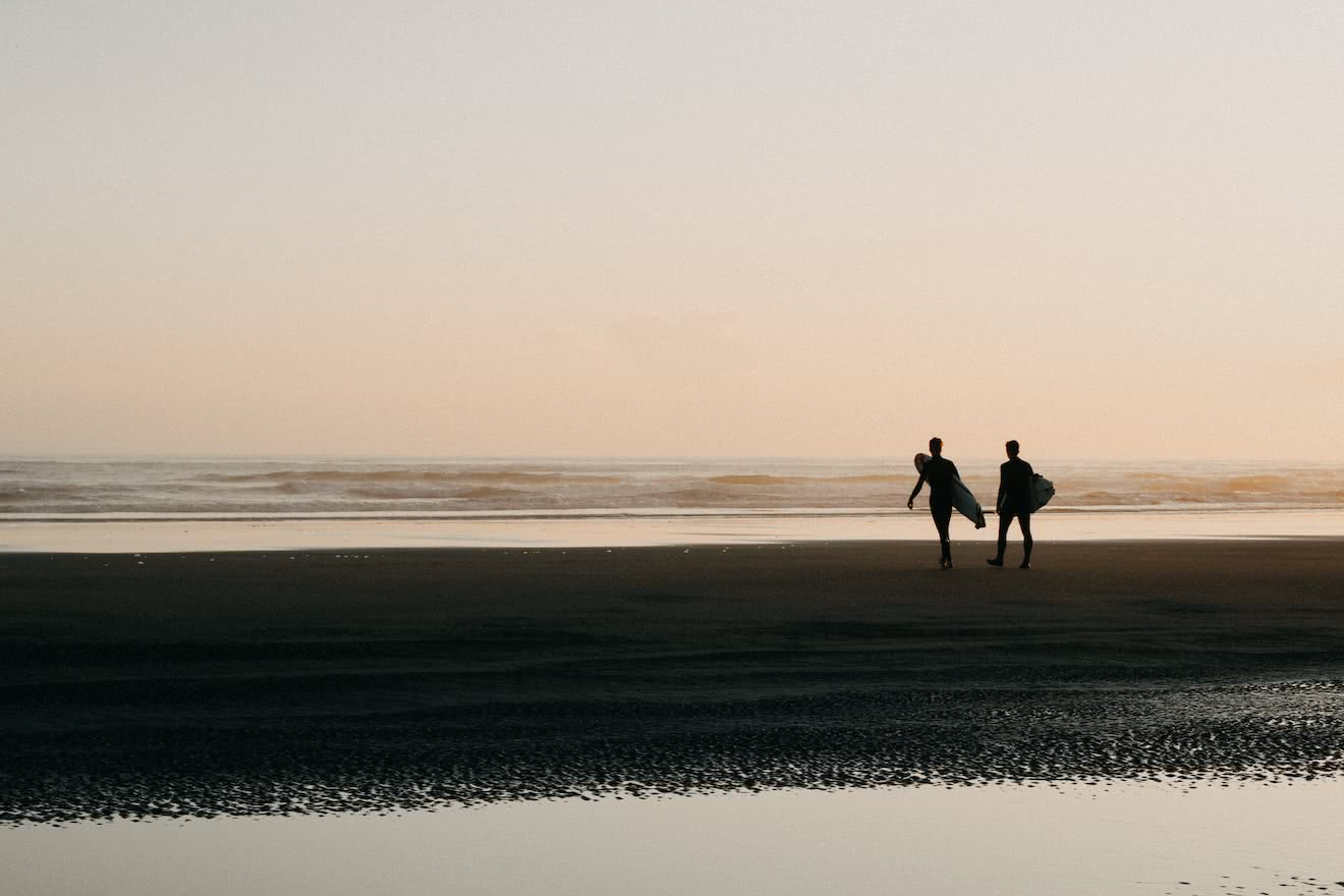 Two surfers on a beach near Tofino, British COlumbia