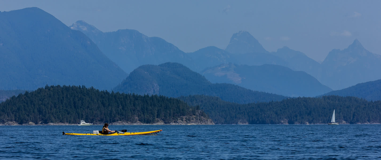 A kayaker paddling with the coast mountains in the distance
