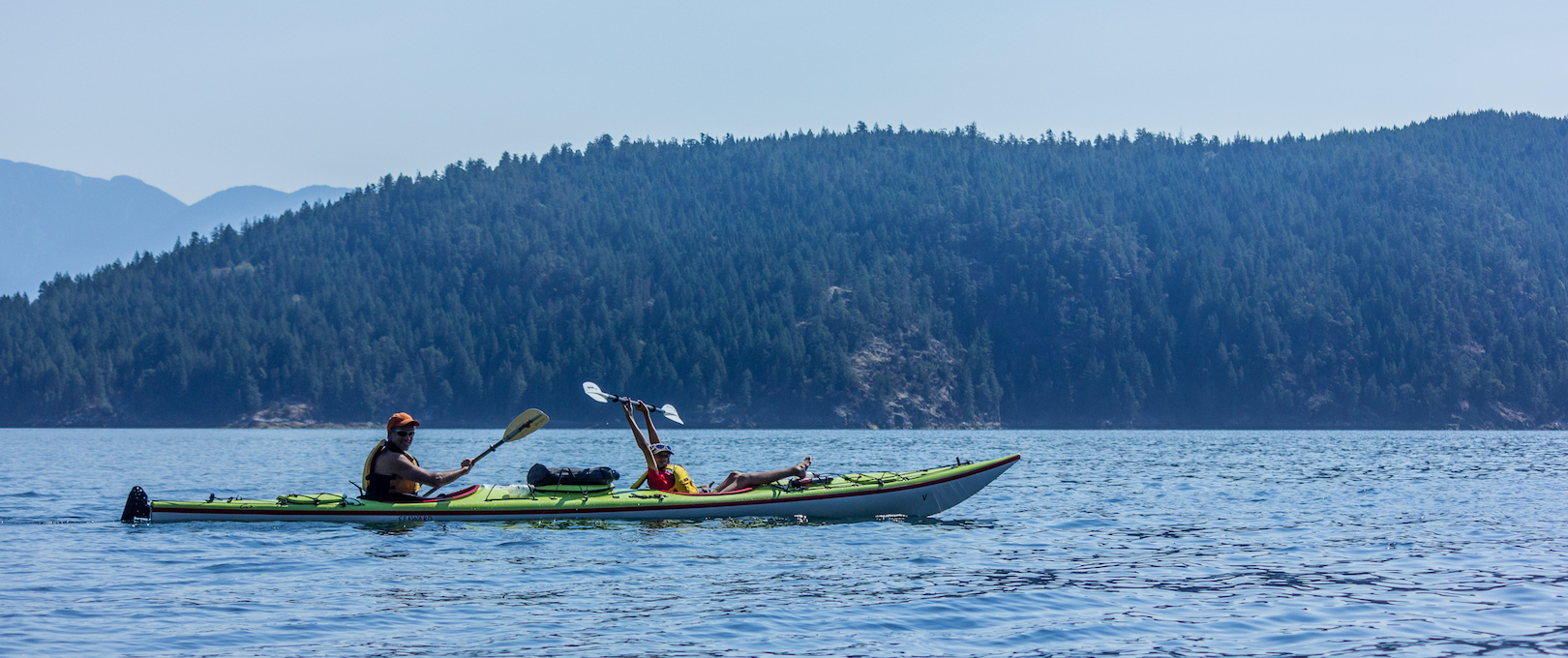A father and son paddling in a double kayak in Desolation Sound