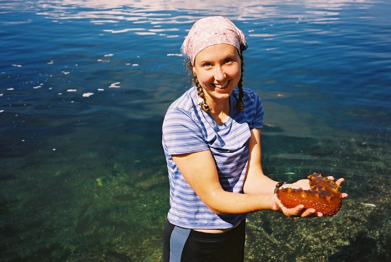 A guide holds a sea cucumber for guests to observe in Desolation Sound