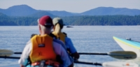 Two guests on a guided kayak tour watching a humpback whale in Desolation Sound
