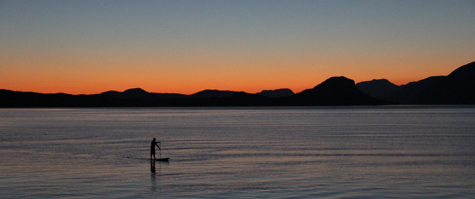 A man on a stand up paddle board with the sun setting behind him in Desolation Sound