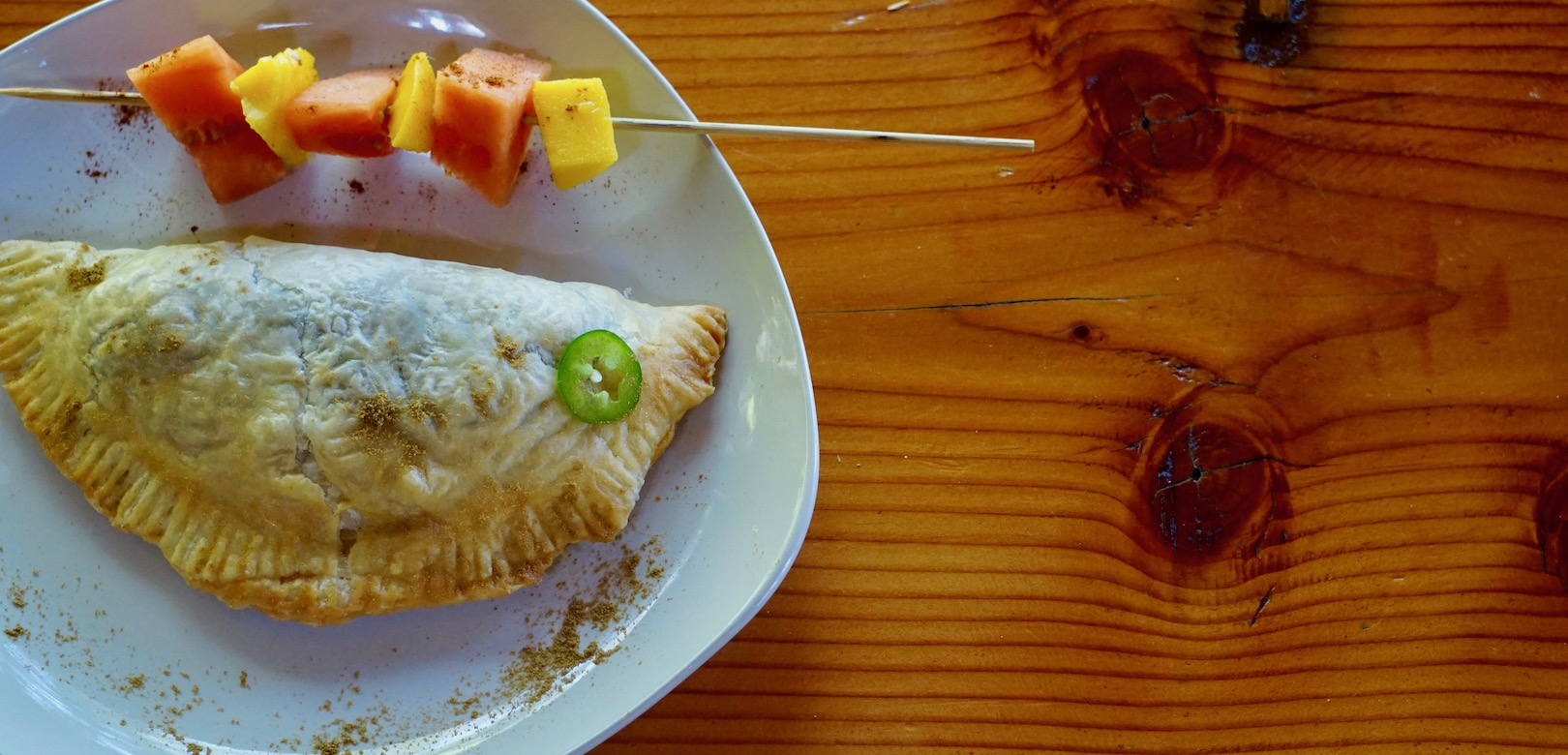 An empanada and fruit skewer plated for lunch at Cabana Desolation Eco Resort
