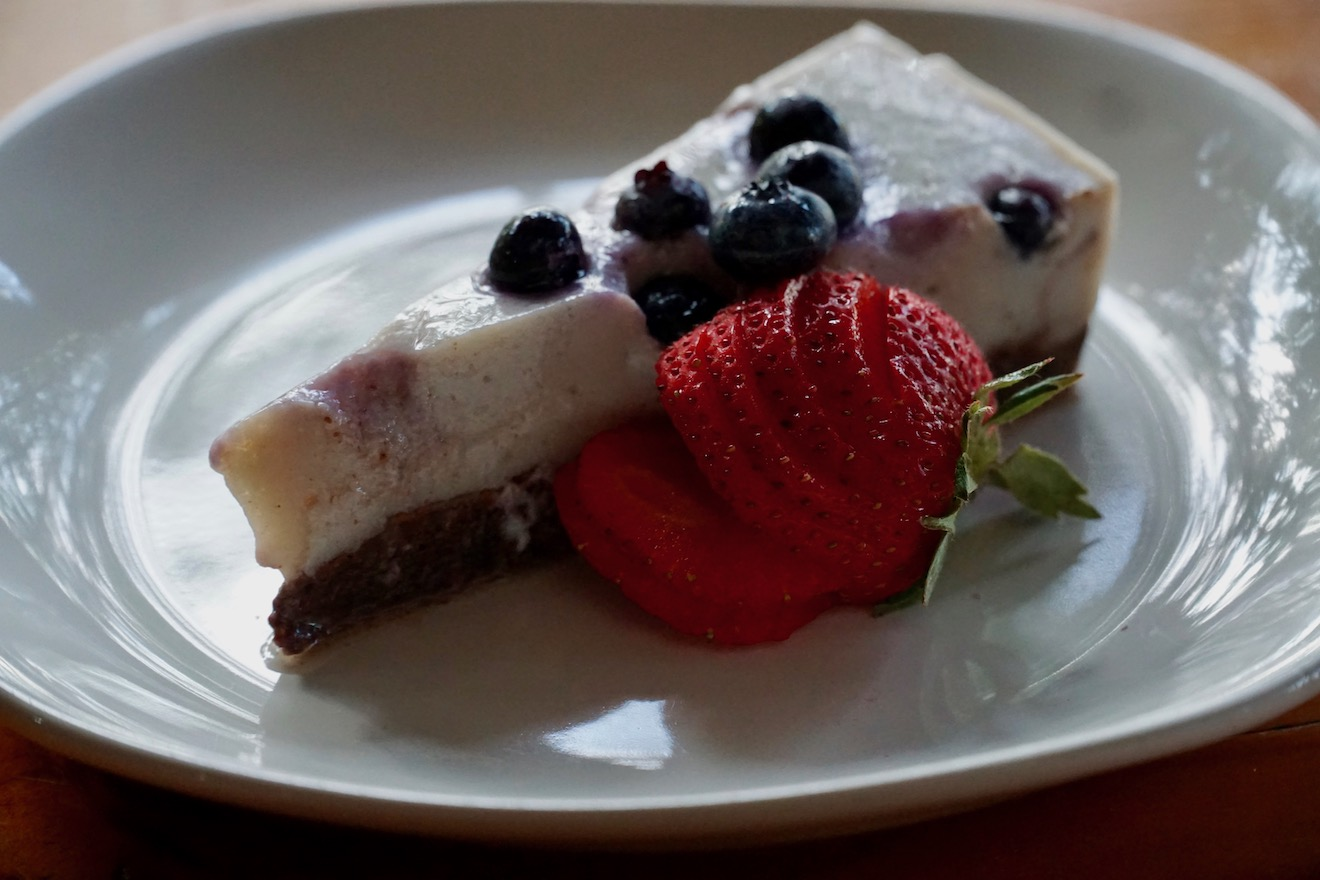 A slice of blueberry cheese cake with a strawberry on the side at the Cabana Cafe